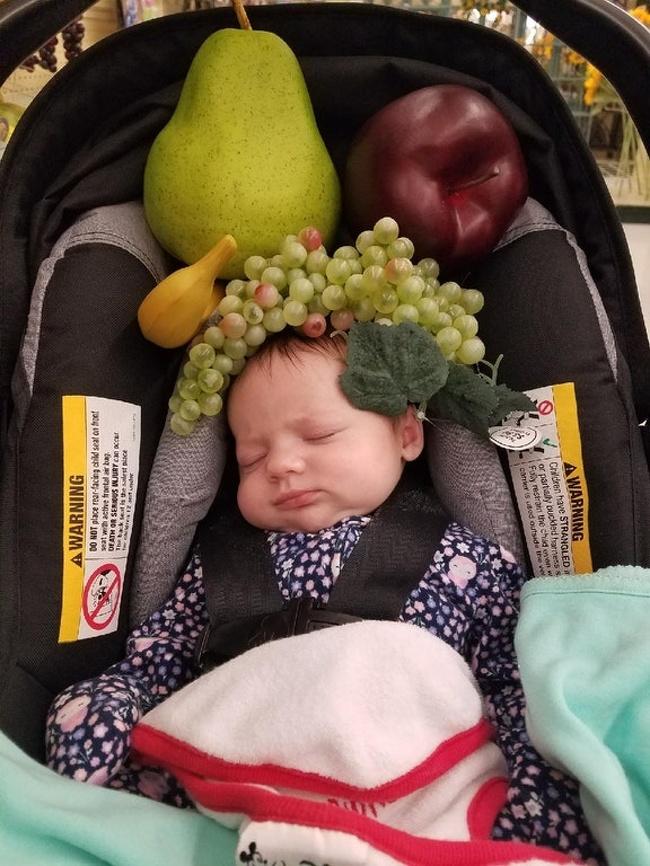 dziecko obłożone owocami na zakupach